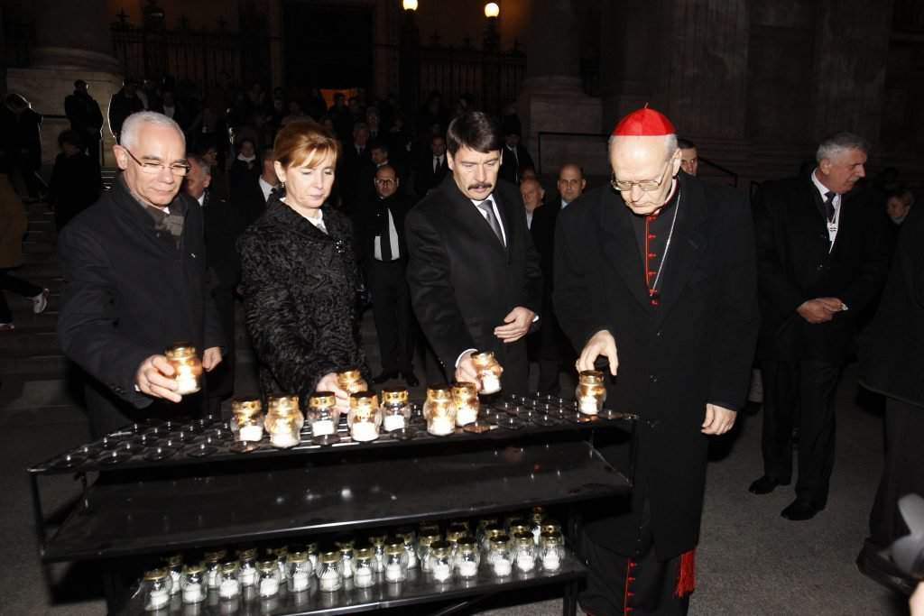 President János Áder and his wife lighting candles for the memory of the victims of the uprising